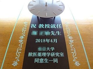 「祝教授就任」「○○先生」「日付」「○○大学○○研究室同窓生一同より」と、前面ガラスに彫刻した振り子型の電波式掛け時計(教授就任のお祝い品)
