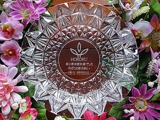 「ロゴマーク」「長い間お疲れさまでした。たばこは控えめに!」「○○様」と、底面に彫刻したガラス製の灰皿(定年退職のお祝い品)
