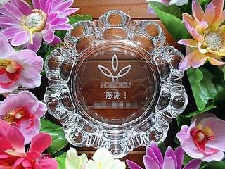 「ロゴマーク、感謝 ○○殿」を底面に彫刻した、永年勤続の記念品用のガラス製灰皿