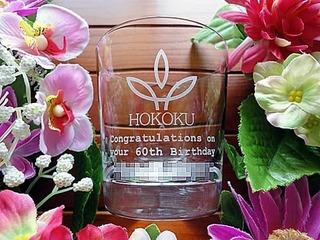 「ロゴマーク」「Congratulations on your 60th birthday」「○○様」と側面に彫刻したロックグラス(社員への還暦祝いの贈り物用)