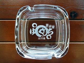 ロゴマークを底面に彫刻した、飲食店の開店祝い用のガラス製灰皿