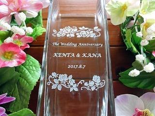 「The wedding anniversary」「奥さまと旦那様の名前」「結婚記念日の日付」「バラの花の飾り」を側面に彫刻した、奥さまへの結婚記念日のプレゼントのフラワーベース