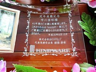 「定年退職記念」「○○様、41年間のご功績に感謝いたします。」「日付」「株式会社○○、代表取締役会長○○」「会社のロゴ」を彫刻した、定年退職の記念品用のガラス製写真立て
