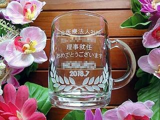 「社会医療法人社団○○、理事就任おめでとうございます。○○様、2018.7」を側面に彫刻した、理事就任祝いの贈り物用のガラス製マグカップ