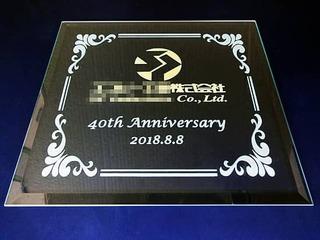 お取引先の会社のロゴマークと名前・40th anniversary・日付を彫刻した、周年祝いの贈り物用のガラス盾