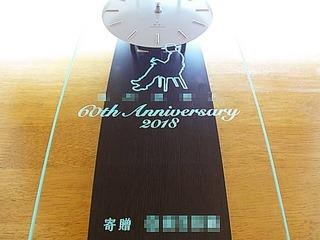 「会社名とマーク、60th anniversary、寄贈 ○○」を彫刻した、お取引先へ贈呈する周年祝い用の掛け時計