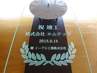「祝竣工、株式会社○○、贈 ○○株式会社」を彫刻した、お取引先の新社屋竣工祝い用の掛け時計