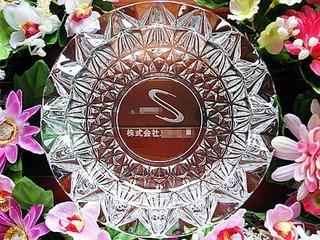 ロゴマークと会社名を底面に彫刻した、お取引先への周年祝い用のガラス製灰皿