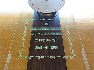「祝 NPO法人○○、日付、職員一同」を彫刻した、NPO法人の周年祝い用の掛け時計