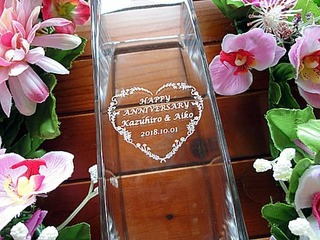 「Happy anniversary、旦那様と奥さまの名前」を彫刻した、結婚記念日のプレゼント用のガラス花器