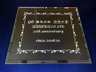 「株式会社○○、10th anniversary」を彫刻した、お取引先への周年祝い用のガラス盾