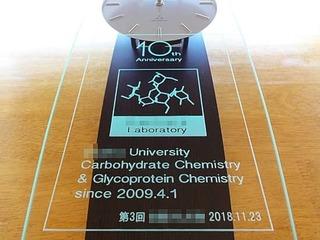 「10th anniversary」「研究室の名前とマーク」を彫刻した、大学の研究室の周年祝い用の掛け時計