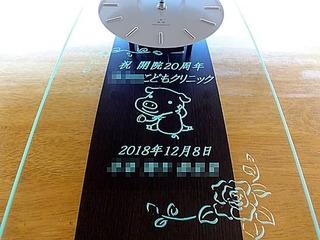 「祝開院20周年、クリニックの名前とイメージキャラクター」を彫刻した、周年祝い用の掛け時計