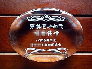 「感謝を込めて ○○先生、○年度○○小学校同窓会」を彫刻した、恩師へのプレゼント用のペーパーウェイト
