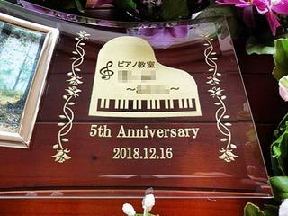 「ロゴマーク、5th anniversary、日付」を彫刻した、ピアノ教室の周年祝い用の写真立て