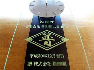 「会社のマーク」と「祝 開設、有限会社○○御中」を彫刻した、営業所の開設祝い用の掛け時計