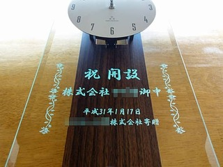「祝開設 株式会社○○御中」を前面ガラスに彫刻した、事業所の開設祝い用の掛け時計