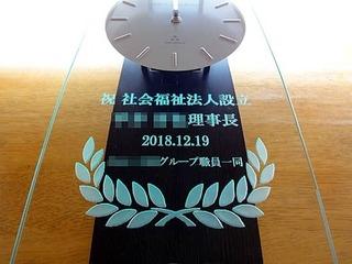 「祝 社会福祉法人設立、○○理事長、日付」を彫刻した、設立祝い用の掛け時計