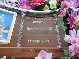 「○○マンション竣工記念、株式会社○○、日付」を彫刻した、竣工祝い用の写真立て