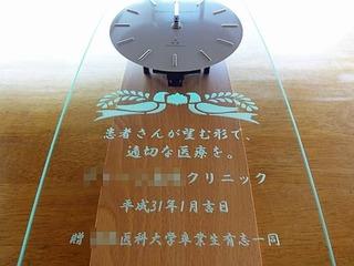 「クリニックの名前、日付、○○大学卒業生有志一同」を彫刻した、開院祝い用の掛け時計