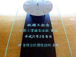 「祝竣工記念、会社名、日付」を彫刻した、営業所の竣工祝い用の名入れ掛け時計