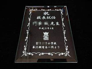 「祝 校長就任 ○○先生、校章、○○一同より」を彫刻した、校長就任祝い用のガラス盾