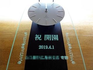 「祝 開園、○○寄贈」を彫刻した、保育園の開園祝い用の掛け時計