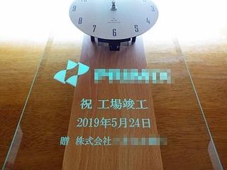 「ロゴマーク」と「祝工場竣工、贈 株式会社○○」を彫刻した、工場竣工祝い用の掛け時計