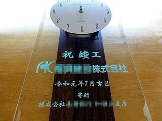 「ロゴマーク」と「祝竣工、寄贈 株式会社○○」を彫刻した、お得意先の本社ビル竣工祝い用の掛け時計