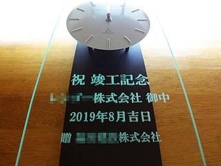 「祝竣工記念、○○株式会社御中、贈 株式会社○○」を彫刻した、お得意先への竣工祝い用の掛け時計