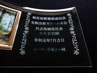 「祝 社屋落成記念、有限会社○○、日付、〇〇一同」を彫刻した、落成祝い用の写真立て