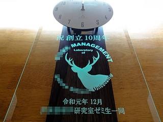 研究室の周年祝い用の掛け時計(研究室のロゴマーク、祝創立10周年 令和元年12月 ○○研究室ゼミ生一同を前面ガラスに彫刻)